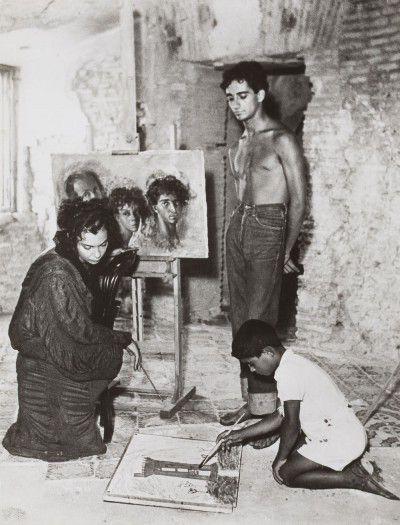 Leonor Fini, Sergio Gajardo, and a stranger in front of Autoportrait avec Sergio et Kot , in Torre San Lorenzo, Italy, 1952