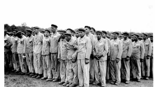 --1938-1941. Φυλακισμένοι σε αναφορά στο στρατόπεδο συγκέντρωσης Μπούχενβαλντ. Οι στολές τους φέρουν τα αναγνωριστικά τριγωνικά σήματα και αριθμούς αναγνώρισης--