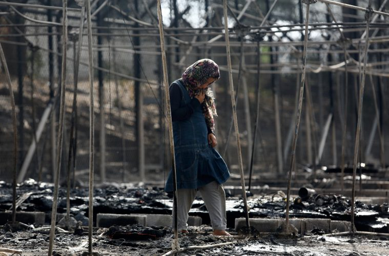 A migrant stands among the remains of a burned tent at the Moria migrant camp, after a fire that ripped through tents and destroyed containers during violence among residents, on the island of Lesbos, Greece, September 20, 2016. REUTERS/Giorgos Moutafis